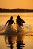 Couple running in lake. Couple at sunset run in the lake Stock Image
