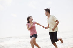 Couple running and laughing by the waters edge on the beach, China Royalty Free Stock Photography
