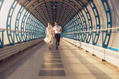 Couple running in long tunnel Royalty Free Stock Photos