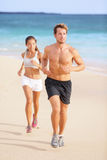 Couple running - man fitness runner first. Couple running - men fitness runner first. Runners in jogging exercise outside on beach. Multiracial couple, Asian stock photo