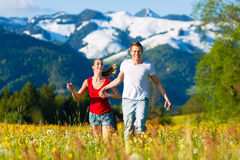 Couple running in the meadow with mountain Stock Image