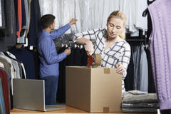 Couple Running Online Clothing Store Packing Goods For Dispatch. Young Couple Running Online Clothing Store Packing Goods For Dispatch Stock Images