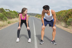 Couple running on the open road together Royalty Free Stock Photos