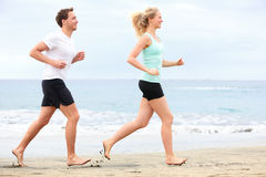 Couple running outdoors on beach. Woman and men runners jogging together outside in full body length Royalty Free Stock Images