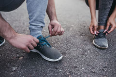 Couple running outdoors. Cropped image of sporty couple is tying shoelaces during run royalty free stock photography