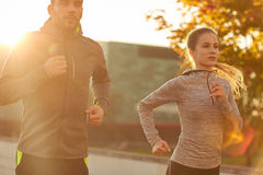 Couple running outdoors. Fitness, sport, people and lifestyle concept - couple running outdoors Stock Photo