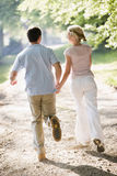 Couple running outdoors holding hands Stock Images