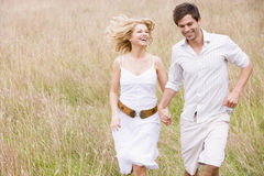 Couple running outdoors holding hands smiling Royalty Free Stock Images