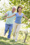 Couple running outdoors in park smiling Royalty Free Stock Photo