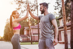 Couple running outdoors. Sporty couple is having rest from running outdoors near modern private houses stock photography