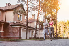 Couple running outdoors. Sporty couple is running outdoors near modern private houses royalty free stock photo