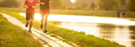 Couple running outdoors, at sunset, by a river. Staying active and fit Royalty Free Stock Images