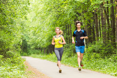 Couple running outdoors. Woman and man runners jogging together outside in full body length. royalty free stock images