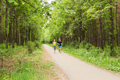 Couple running outdoors. Woman and man runners jogging together outside in full body length. stock photos
