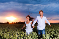 Couple is running over grainfield at night Stock Photography