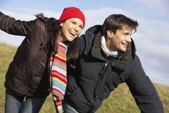 Couple Running In The Park. Wearing Winter Clothes Stock Photo