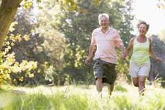 Couple running in park holding hands and smiling.  Stock Images