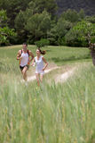 Couple running on path through rural field stock image