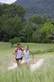 Couple running on path through rural field royalty free stock photography