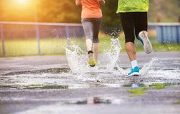 Couple running in rainy weather. Young couple jogging on asphalt in rainy weather royalty free stock photo