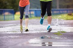 Couple running in rainy weather Royalty Free Stock Photos