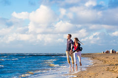 Couple running through sand and waves at beach Royalty Free Stock Photo