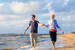 Couple running through sand and waves at beach Royalty Free Stock Images