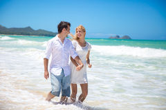 Couple running on a sandy beach Stock Photos
