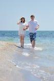Couple running on a sandy beach Stock Photo