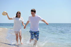 Couple running on a sandy beach Royalty Free Stock Photo