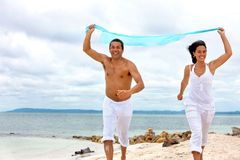 Couple running with sarong Stock Photography