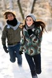 Couple running in the snow. Young couple running in the snow Royalty Free Stock Image