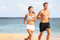 Couple running - sport runners jogging on beach. Couple running. Sport runners jogging on beach working out smiling happy. Fit male fitness model and attractive Stock Photography