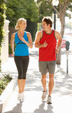 Couple running on street in city Royalty Free Stock Photos