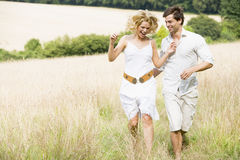 Couple running through summer field Royalty Free Stock Image