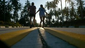 Couple running on sunny road between the palm trees. slow motion. 1920x1080. Hd stock footage