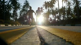 Couple running on sunny road between the palm trees. slow motion. 1920x1080. Hd stock video