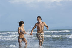 Couple Running In Surf At Beach Stock Photos