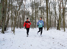 Couple running and talking in winter Stock Photo
