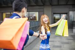 Couple running to the mall and showing shopping bags. Happy couple running to the mall and showing shopping bags Royalty Free Stock Photo