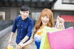 Couple running to the mall and showing shopping bags. Happy couple running to the mall and showing shopping bags Stock Photos