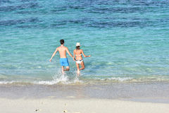 Couple running to the turquoise seawater Stock Image