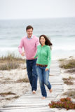 Couple running together along beach path Stock Photo