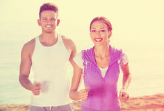 Couple running together on beach by ocean Royalty Free Stock Photos