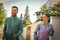 Couple running together. Close up. Couple running together. Young couple jogging together trough city park Royalty Free Stock Images