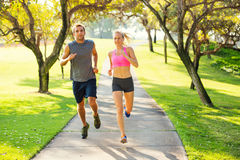 Couple running together in the park. Athletic couple running together. Sport runners jogging on park trail in the early morning.  Healthy lifestyle fitness Stock Image