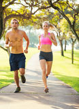 Couple running together in the park. Athletic couple running together. Sport runners jogging on park trail in the early morning.  Healthy lifestyle fitness Royalty Free Stock Photo