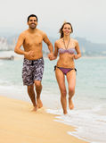 Couple running together on the sea beach Royalty Free Stock Image