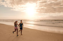 Couple running together on the sea shore Stock Images