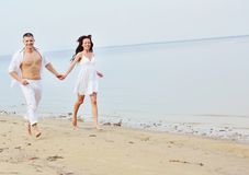 Couple running  together  at seaside Royalty Free Stock Photography